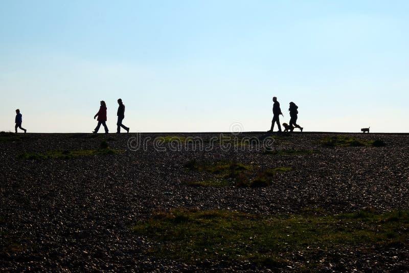 Μια παραλία χαλικιών και unrecognisable άνθρωποι που περπατούν στον ορίζοντα στοκ εικόνα με δικαίωμα ελεύθερης χρήσης
