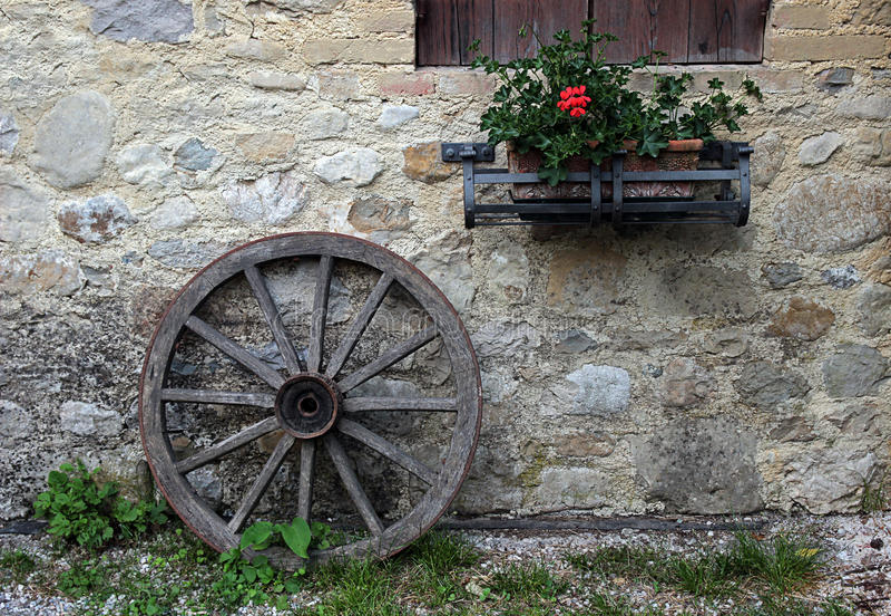Μια παλαιά ξύλινη ρόδα που κλίνει ενάντια σε έναν τοίχο πετρών στοκ εικόνες