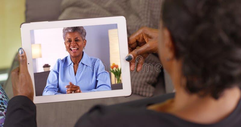 Μια παλαιότερη μαύρη γυναίκα που μιλά στο φίλο της μέσω της τηλεοπτικής συνομιλίας στοκ εικόνα