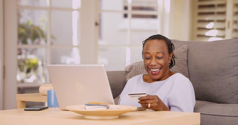 Μια παλαιότερη μαύρη γυναίκα πληρώνει τους λογαριασμούς της στο lap-top της στοκ εικόνα