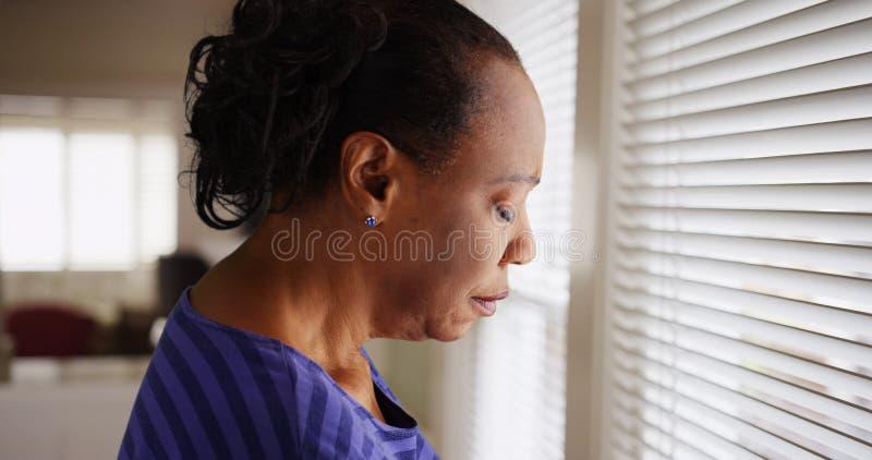 Μια παλαιότερη μαύρη γυναίκα φαίνεται mournfully έξω το παράθυρό της στοκ φωτογραφίες