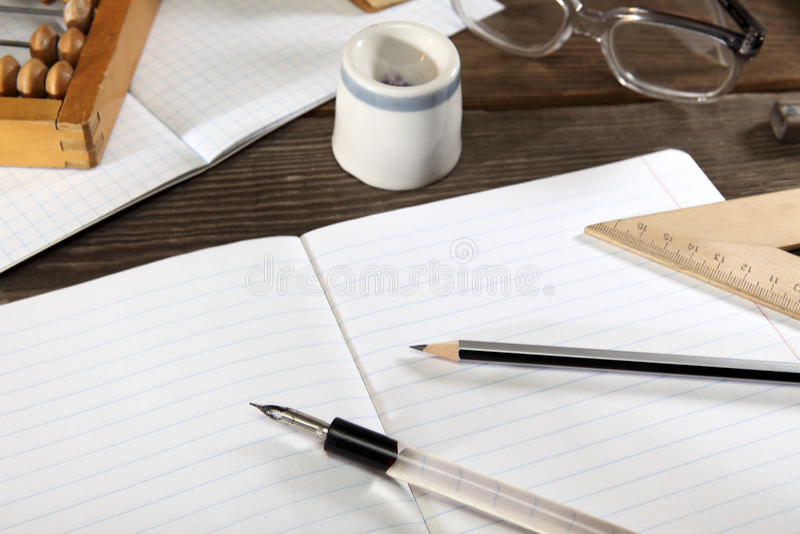 Μια πενοθήκη με μια μάνδρα, ένα απλός μολύβι, straightedge, ένας άβακας και τα γυαλιά βρίσκονται σε ένα ανοικτό σημειωματάριο Ανα στοκ φωτογραφία με δικαίωμα ελεύθερης χρήσης