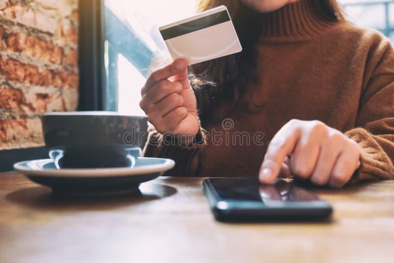 Μια πιστωτική κάρτα εκμετάλλευσης γυναικών και υπόδειξη στο κινητό τηλέφωνο για να ψωνίσει on-line στοκ εικόνα