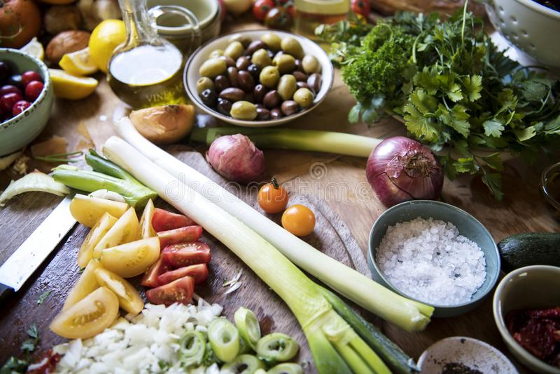 Μια πολυάσχολη κορυφή κουζινών με το λαχανικό και τα συστατικά στοκ εικόνα