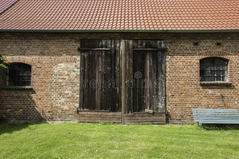 Μια πρόσοψη μιας παλαιάς σιταποθήκης τουβλότοιχος με την κεραμωμένη στέγη, και ξύλινη πόρτα στοκ φωτογραφία