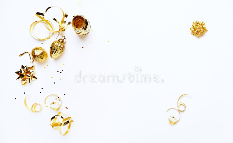 Μια ρύθμιση των χρυσών διακοσμήσεων Χριστουγέννων στο άσπρο υπόβαθρο flatlay διάστημα αντιγράφων στοκ εικόνα
