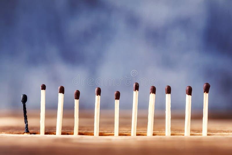 Μια σειρά των αντιστοιχιών σε ένα ξύλινο υπόβαθρο, η τελευταία αντιστοιχία έκαψε το δ στοκ εικόνες με δικαίωμα ελεύθερης χρήσης