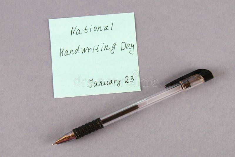 Μια σημείωση με μια επιγραφή είναι μια εθνική μέρα του γραψίματος χεριών και μια μάνδρα σε ένα γκρίζο υπόβαθρο στοκ φωτογραφία με δικαίωμα ελεύθερης χρήσης