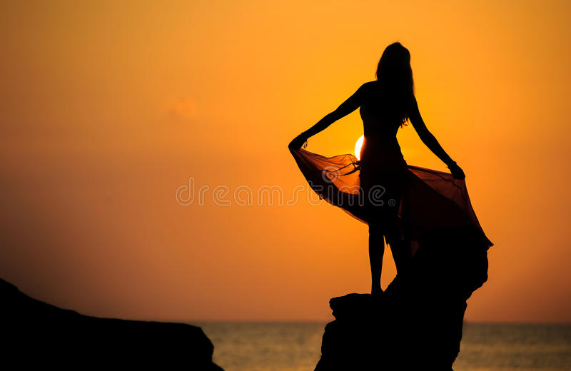 Μια σκιαγραφία ενός νέου κοριτσιού στο βράχο στο ηλιοβασίλεμα 1 στοκ εικόνες