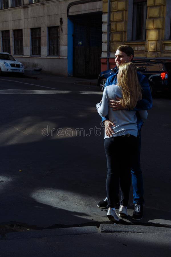 μια σκοτεινή ανασκόπηση Μια αγάπη και ένα ευτυχές ζεύγος αγκαλιάζουν στην οδό, ανάμεσα σε ένα κόκκινο αυτοκίνητο, τα χαμόγελα τύπ στοκ εικόνα