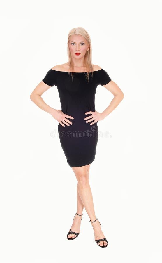 Μια σοβαρή κοιτάζοντας ξανθή γυναίκα που στέκεται στη μαύρη εξάρτηση στοκ εικόνες με δικαίωμα ελεύθερης χρήσης