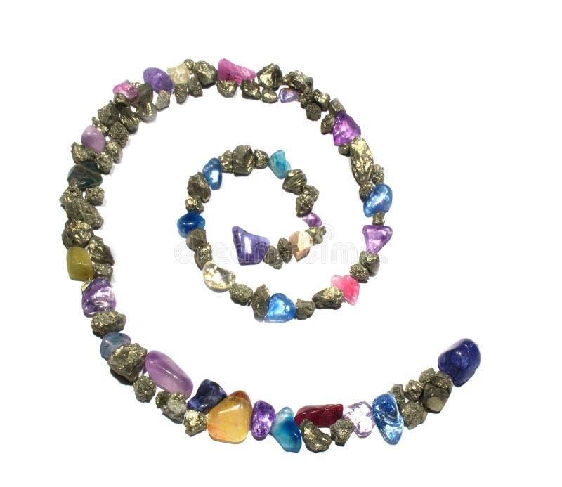 Μια σπείρα των χρυσών λαμπρών βράχων και των πολύτιμων λίθων, που διαμορφώνει ένα σύμβολο στοκ εικόνα με δικαίωμα ελεύθερης χρήσης