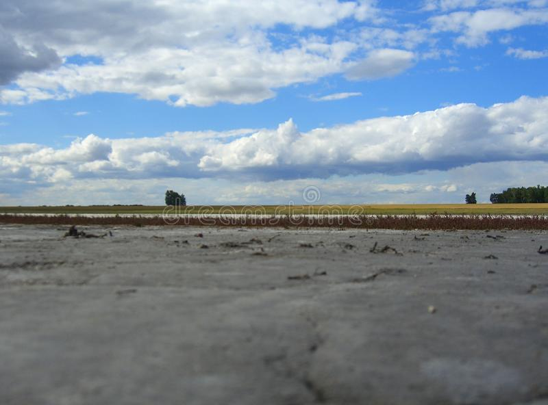 Μια στεγνωμένη κοίτη ποταμού της αλατισμένης λίμνης εγκαταλείπει το γυμνό κατώτατο σημείο της δεξαμενής στο Καζακστάν με το τοπίο στοκ φωτογραφία με δικαίωμα ελεύθερης χρήσης