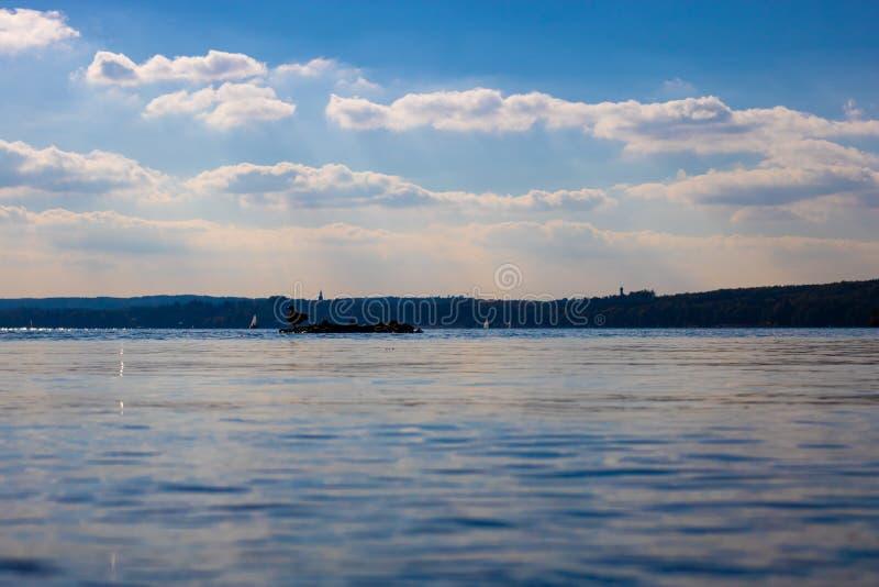 Μια συμπαθητική άποψη σχετικά με μια ήρεμη λίμνη με μια πάπια σε μερικές πέτρες στοκ φωτογραφία