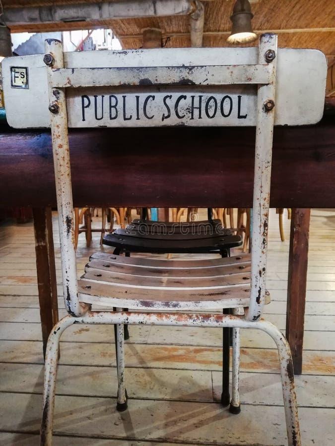 Μια συμπαθητική παλαιά καρέκλα μελέτης μπροστά από ένα γραφείο με το δημόσιο σχολείο λέξεων που τυπώνεται στην πλάτη στοκ εικόνες με δικαίωμα ελεύθερης χρήσης