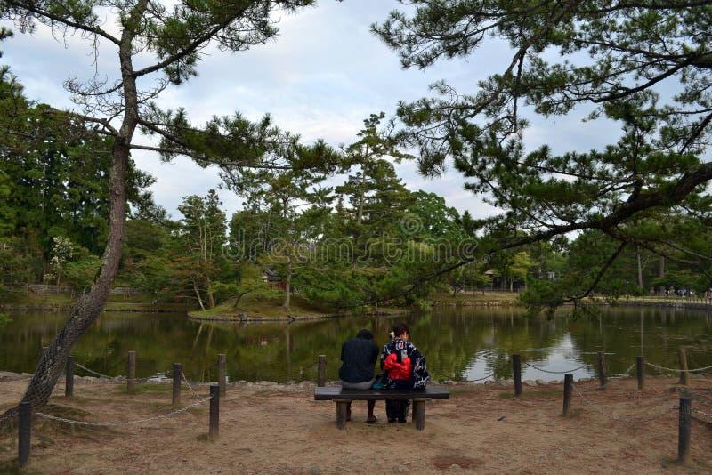 Μια συνεδρίαση ζευγών σε έναν κήπο με το yukata τους, ένα ιαπωνικό tradi στοκ φωτογραφίες
