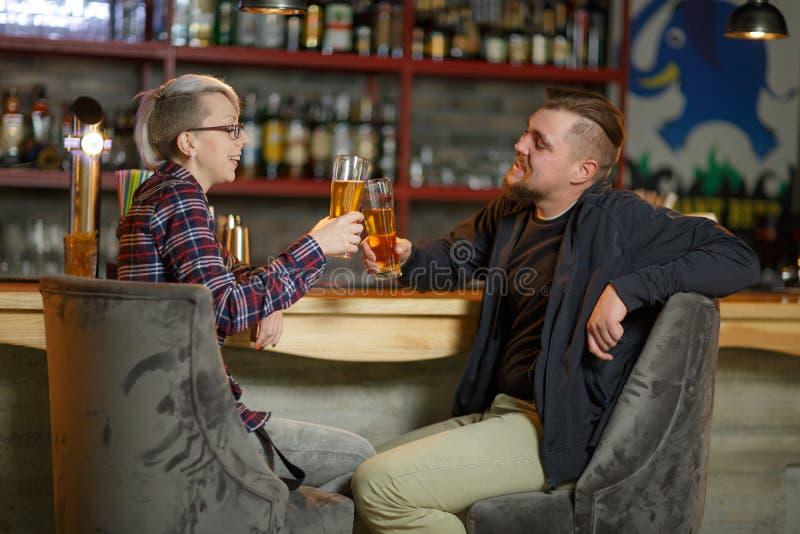 Μια συνεδρίαση ζευγών σε έναν φραγμό, να κουβεντιάσει και ευθυμίες με τα ποτήρια της μπύρας indoors στοκ φωτογραφίες με δικαίωμα ελεύθερης χρήσης