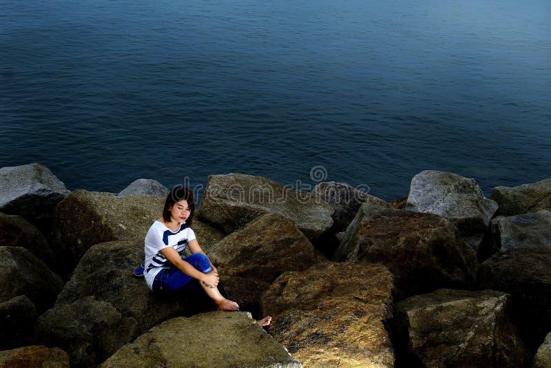 Μια συνεδρίαση γυναικών στις πέτρες στην παραλία στοκ εικόνες