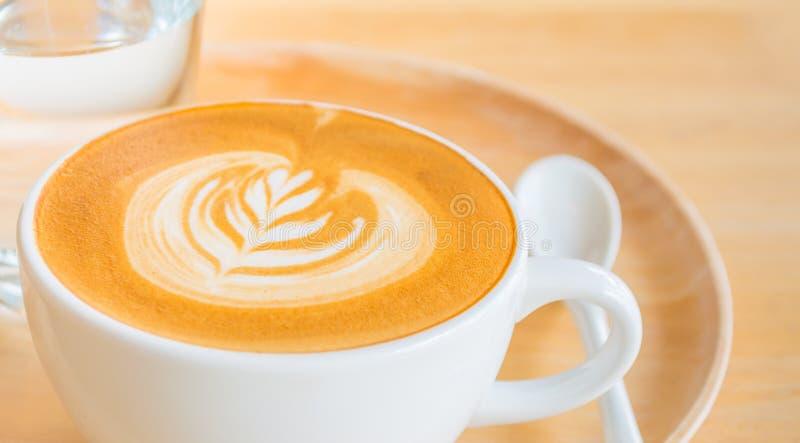 Μια τέχνη καφέ Latte στο ξύλινο γραφείο στοκ φωτογραφίες