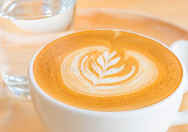 Μια τέχνη καφέ Latte στο ξύλινο γραφείο στοκ εικόνα με δικαίωμα ελεύθερης χρήσης