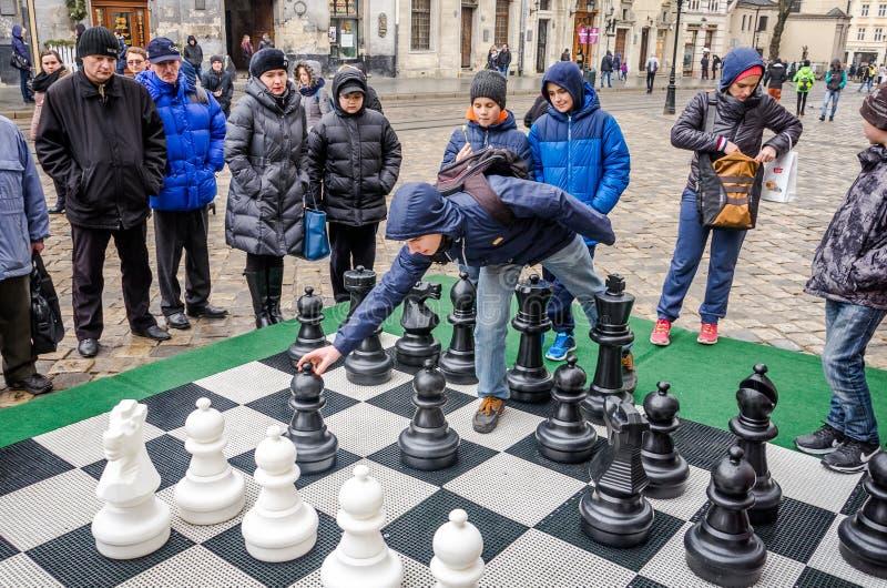 Μια τεράστια σκακιέρα στην οποία η μάχη στα παιδιά πρωταθλημάτων που παίζουν με τα άσπρα και μαύρα κομμάτια υπαίθρια στην οδό στοκ εικόνες με δικαίωμα ελεύθερης χρήσης