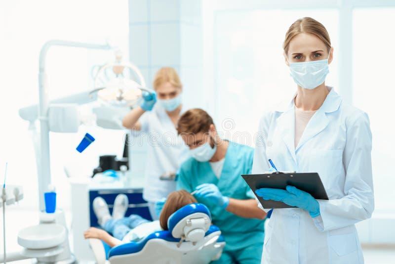 Μια τοποθέτηση νοσοκόμων σε ένα κλίμα των οδοντιάτρων που μεταχειρίζονται το τα δόντια κοριτσιών ` s Φορά μια ιατρική μάσκα στοκ φωτογραφία με δικαίωμα ελεύθερης χρήσης