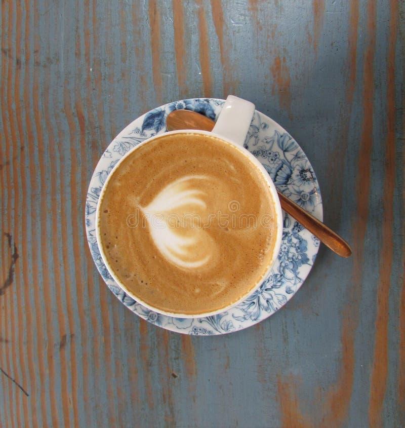 Μια τοπ άποψη ενός φλυτζανιού του καφέ cuppachino στον ξύλινο πίνακα με το κουτάλι στοκ φωτογραφίες με δικαίωμα ελεύθερης χρήσης