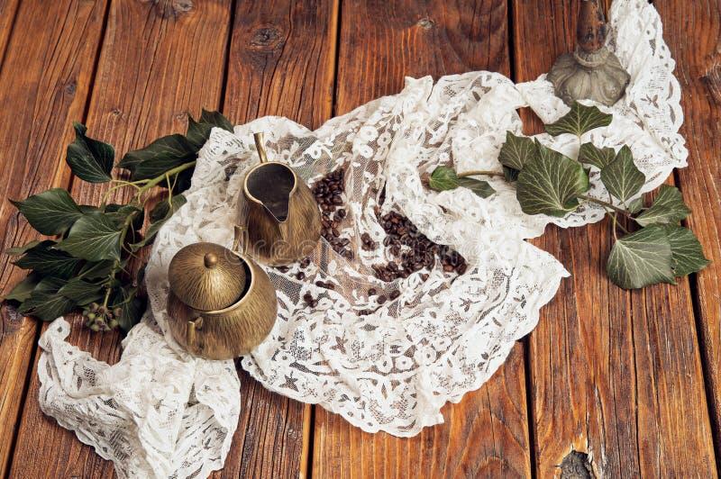 Μια τοπ άποψη μιας κανάτας γάλακτος ορείχαλκου και μια ζάχαρη ορείχαλκου κυλούν, παρουσιασμένος σε μια παλαιά, ξύλινη επιτραπέζια στοκ εικόνες με δικαίωμα ελεύθερης χρήσης