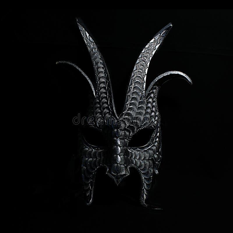 Μια τρομακτική μάσκα αποκριών σε γραπτό σε ένα μαύρο κλίμα στοκ εικόνες