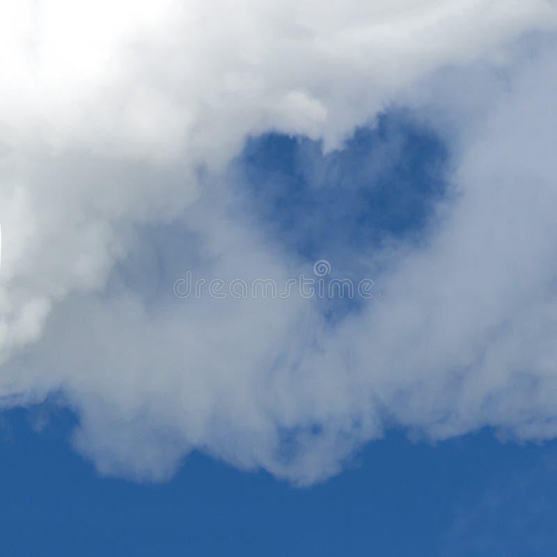 Μια τρύπα υπό μορφή καρδιάς σε ένα άσπρο σύννεφο ενάντια σε έναν μπλε ουρανό Μια τετραγωνική εικόνα Ανασκόπηση για το σχέδιο διάσ στοκ εικόνες