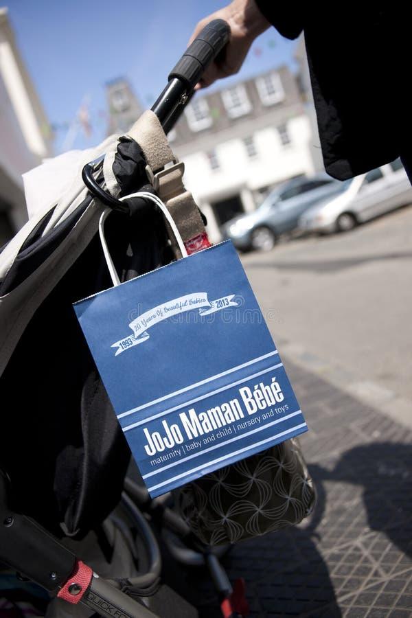 Μια τσάντα αγορών της Jojo Maman Bebe κρέμασε σε ένα καροτσάκι στις οδούς του λιμένα του ST Peter, Guernsey, τα νησιά καναλιών, U στοκ εικόνες