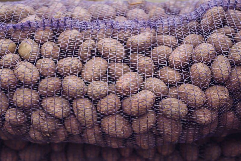 Μια τσάντα των ακατέργαστων και βρώμικων πατατών Φρέσκια κινηματογράφηση σε πρώτο πλάνο πατατών σε ένα πλέγμα στοκ εικόνα με δικαίωμα ελεύθερης χρήσης