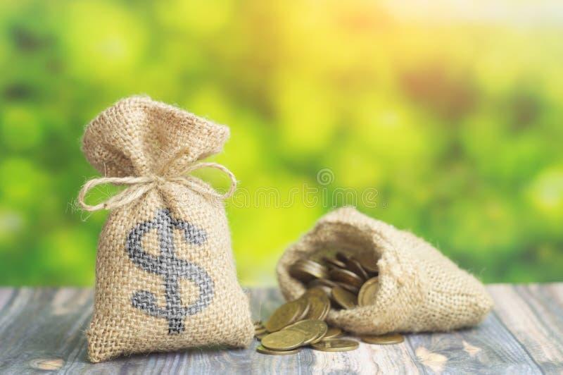 Μια τσάντα χρημάτων με το σημάδι δολαρίων και τσάντα με τα νομίσματα στο πράσινο υπόβαθρο Έννοια της χρηματοδότησης δανείου ή επι στοκ φωτογραφίες