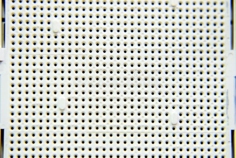 Μια υποδοχή κάτω από τον επεξεργαστή του υπολογιστή, τρύπες κάτω από τα πόδια των επαφών Ηλεκτρονικός πίνακας με ηλεκτρικό στοκ εικόνα με δικαίωμα ελεύθερης χρήσης