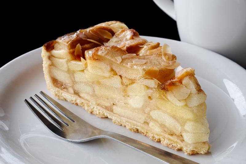 Μια φέτα της πίτας μήλων στο άσπρο κεραμικό πιάτο με το δίκρανο Μαύρη ΤΣΕ στοκ φωτογραφίες με δικαίωμα ελεύθερης χρήσης