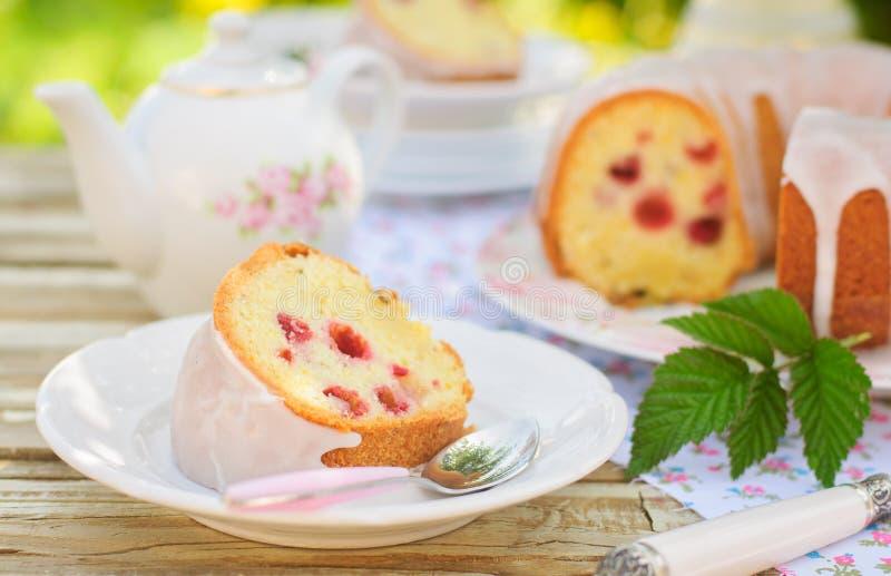 Μια φέτα του κέικ Bundt σπόρου λεμονιών και του κυμινοειδούς κάρου με τα σμέουρα στοκ εικόνες