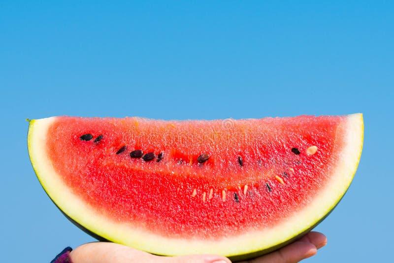 Μια φέτα του κόκκινου καρπουζιού που κατέχει ένα χέρι επάνω στο μπλε ουρανό το καλοκαίρι στοκ φωτογραφία