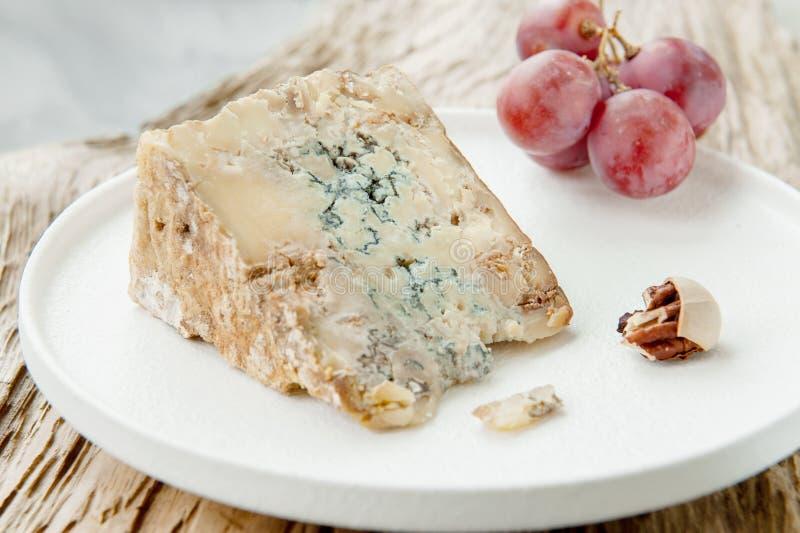 Μια φέτα του μπλε ηλικίας τυριού Stilton σε έναν ξύλινο πίνακα Το τυρί εξυπηρετείται με τα μεγάλα σταφύλια Ποιότητα των αγροτικών στοκ εικόνες