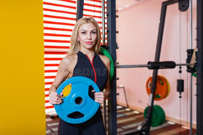 Μια φίλαθλη γυναίκα στέκεται κοντά στον προσομοιωτή και κρατά μια μπλε ράβδο τηγανιτών στη γυμναστική στοκ φωτογραφία με δικαίωμα ελεύθερης χρήσης