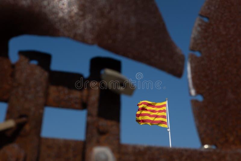 Μια φορεμένη καταλανική σημαία ορατή μέσω οξυδωμένο καιρικό vane μετάλλων στην κορυφή Begur Castle, Καταλωνία, Ισπανία στοκ εικόνες