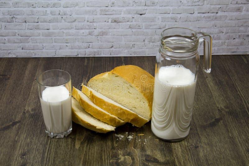 Μια φραντζόλα του άσπρου ψωμιού που τεμαχίζεται με ένα ποτήρι καραφών του γάλακτος σε έναν πίνακα των καφετιών πινάκων στοκ εικόνες