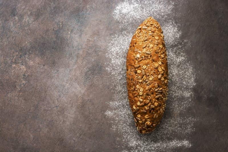 Μια φραντζόλα του φρέσκου ψωμιού με τους σπόρους ηλίανθων, σουσάμι σε ένα σκοτεινό αγροτικό υπόβαθρο E στοκ εικόνες με δικαίωμα ελεύθερης χρήσης