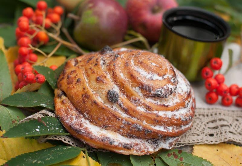 Μια φωτεινή σύνθεση με ένα φλυτζάνι του ισχυρού μαύρου τσαγιού, γλυκό κουλούρι με τις σταφίδες, τα μούρα τέφρας, τα μήλα και τα ζ στοκ φωτογραφία με δικαίωμα ελεύθερης χρήσης