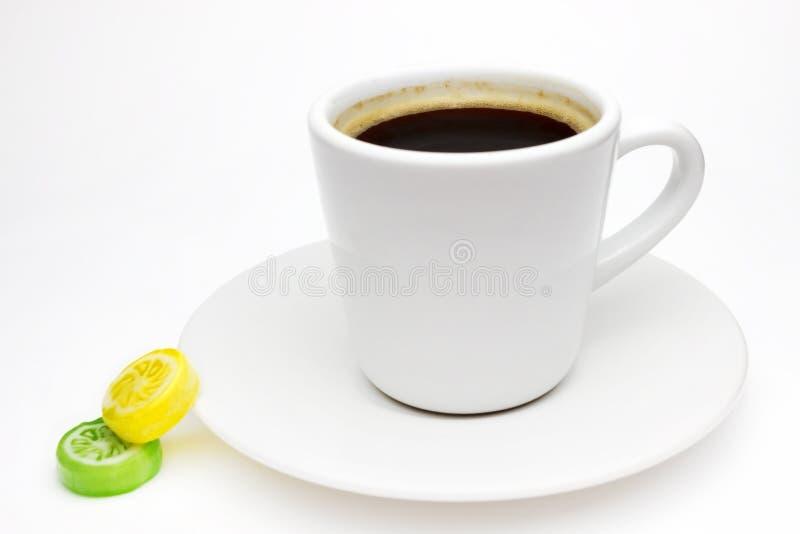 Μια φωτογραφία του άσπρου φλυτζανιού καφέ πορσελάνης σας σε πιάτο και δύο ζωηρόχρωμες κίτρινες και πράσινες καραμέλες ζάχαρης εσπ στοκ εικόνες με δικαίωμα ελεύθερης χρήσης