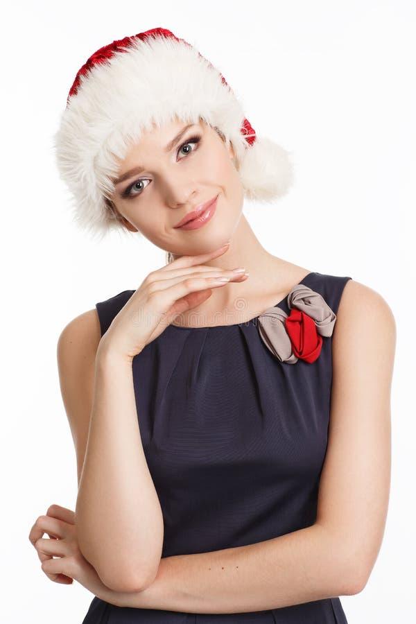 Μια χαμογελώντας νέα γυναίκα σε ένα καπέλο Χριστουγέννων στοκ εικόνες