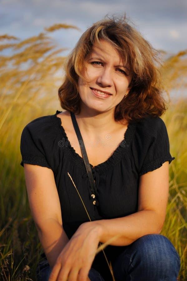 Μια χαριτωμένη μέσης ηλικίας γυναίκα στηρίζεται στο πάρκο στοκ φωτογραφία με δικαίωμα ελεύθερης χρήσης