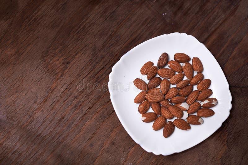 Μια χούφτα των αμυγδάλων στο πιάτο στοκ εικόνα με δικαίωμα ελεύθερης χρήσης