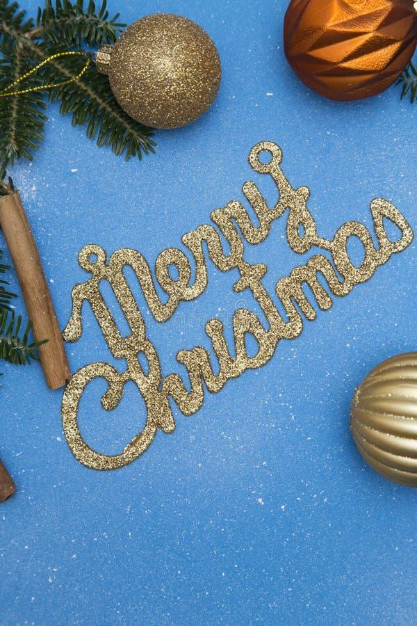 Μια χρυσή gleaming επιγραφή Χαρούμενα Χριστούγεννας σε ένα μπλε υπόβαθρο στοκ φωτογραφίες
