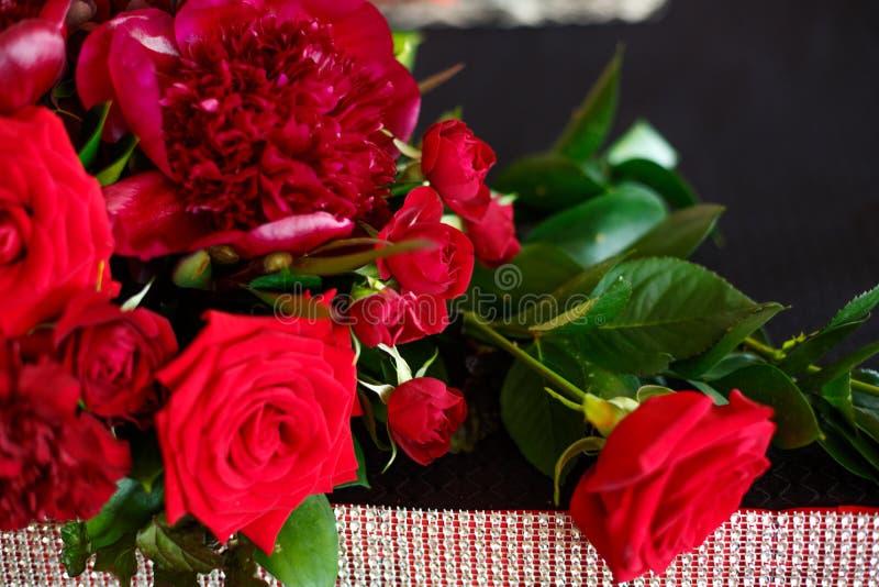 Μια όμορφη ανθοδέσμη των κόκκινων τριαντάφυλλων και peonies είναι στον πίνακα στοκ φωτογραφία με δικαίωμα ελεύθερης χρήσης