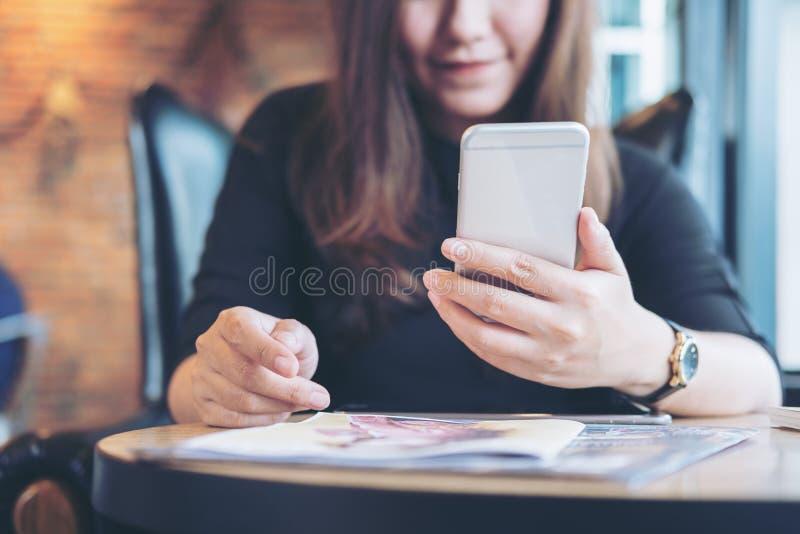 Μια όμορφη ασιατική γυναίκα με το πρόσωπο smiley που κρατά και που χρησιμοποιεί το έξυπνο τηλέφωνο με τα περιοδικά στοκ φωτογραφίες με δικαίωμα ελεύθερης χρήσης